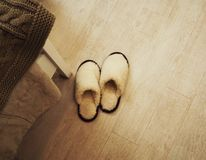 Pair of fluffy cozy slippers on the floor in bedroom stock photos