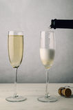 Pair of Fluted Champagne Glasses Being Filled on Wood Plank Tabl Stock Photo