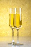 A pair of flutes of champagne on golden abstract background Royalty Free Stock Images