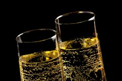 A pair of flutes of champagne with golden bubbles Royalty Free Stock Photography