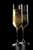 A pair of flutes of champagne with golden bubbles on black wood background