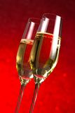 A pair of flutes of champagne red abstract background Stock Photography