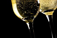 A pair of flutes of champagne tilted with golden bubbles Royalty Free Stock Photography