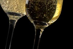 A pair of flutes of champagne tilted with golden bubbles Stock Images