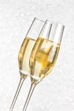 A pair of flutes of golden champagne on silver bokeh Royalty Free Stock Photography