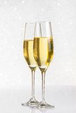 A pair of flutes of golden champagne on silver bokeh Royalty Free Stock Images