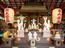 A pair of fox statues in front of a small temple in kiyomizu tem. Kyoto,Japan - June 28, 2014 : A pair of fox statues in front of a small temple in kiyomizu Royalty Free Stock Photos
