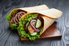 Pair of fresh juicy wrap sandwiches with chicken and vegetables Stock Photos