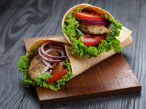 Pair of fresh juicy wrap sandwiches with chicken and vegetables Stock Image