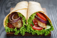 Pair of fresh juicy wrap sandwiches with chicken and vegetables Royalty Free Stock Images
