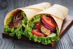 Pair of fresh juicy wrap sandwiches with chicken and vegetables Royalty Free Stock Photography