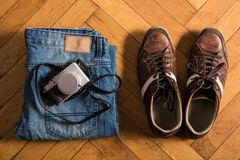 Blue jeans, brown shoes, and a camera Stock Photo