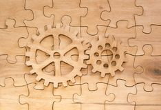 Pair of gears on the assembled group of puzzles. Of wood. movement, thought process Stock Images