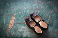 Pair of Girl Shoes on old blackboard Stock Image