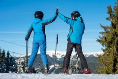 Pair giving high five to each other, smiling, standing with skis on mountain top at a winter resort with ski lifts. Mountains and blue sky in background. View royalty free stock photo