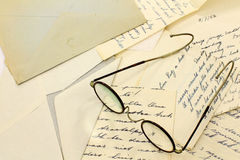 A pair of  glasses. A pair of old glasses on some old letters and an envelope Stock Photos