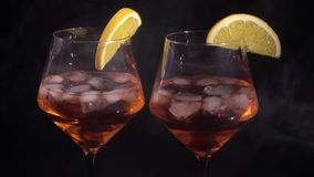 Pair of glasses with alcoholic drink beverage wine. Cocktail black background isolated with smoke stock footage