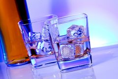 A pair of glasses of alcoholic drink with ice on disco blue light Royalty Free Stock Photos