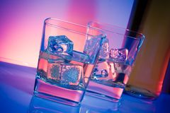 A pair of glasses of alcoholic drink with ice on disco violet light Royalty Free Stock Photos