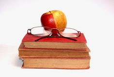 A pair of glasses and a apple. Also some books Stock Photos