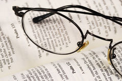 A pair of glasses on a book of knowledge Stock Image