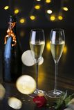 A pair of glasses of champagne with a rose on a table and a bottle of champagne. festive picture. Closeup of a pair of wine glasses, dinning and night life royalty free stock image