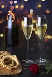 A pair of glasses of champagne with a rose on a table, a sweet cake and a bottle of champagne. festive picture stock image