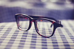 Pair of glasses on a checkered table cloth. Pair of tortoise shell glasses on a checkered table cloth royalty free stock photography