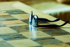 Pair of glasses on a checkered table. Eyecare concept. Pair of stylish glasses on a checkered table stock image