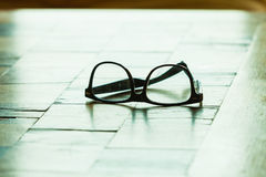 Pair of glasses on a checkered table. Eyecare concept. Pair of stylish glasses on a checkered table stock images