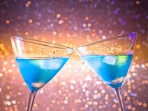 A pair of glasses of  fresh blue cocktail with ice make cheers Stock Photos