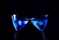 A pair of glasses of  fresh cocktail with ice make cheers. On blue tint light with space for text Stock Photography