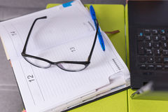Pair of glasses and a pen on a journal lying on the laptop table royalty free stock photo
