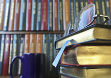 A Pair of Glasses on a Stack of Books. A Pair of Silver Glasses on a Stack of Leather Bound Books in a Library Stock Photo