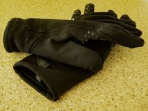 A pair of glove on a counter. In black colors, we can see the wear of this cloth. In Quebec we need it for the cold seasons. Ulverton, Quebec, Canada; December 4 royalty free stock photography