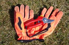 A pair of gloves and a pruning shear. With garden gloves and a pruning shear can you cut bushes in the garden Stock Photo
