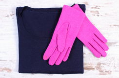 Pair of gloves and sweater for woman on old wooden background Royalty Free Stock Images