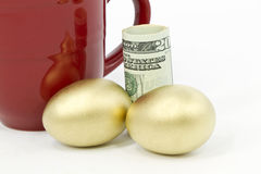 Pair of gold eggs, dollar currency, and red mug Royalty Free Stock Photo