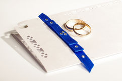 Pair of gold rings on the wedding invitation Stock Images
