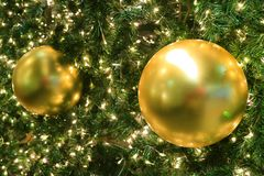 Pair of gold shiny ball Christmas ornaments on sparkling Christmas tree. Blurred background Royalty Free Stock Images