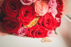 A pair of gold wedding rings lies next to the bouquet of the bride. Soft focus, toned picture. Close-up royalty free stock images