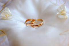 Pair of gold wedding rings on a white pillow Stock Photo
