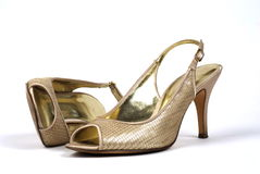 Pair of Gold Women's High-Heel Shoes. A pair of gold women's high-heel shoes against white background, one shoe standing, one shoe lying Stock Images