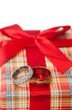 Pair of golden rings with orange rose on the red gift box with r Stock Image