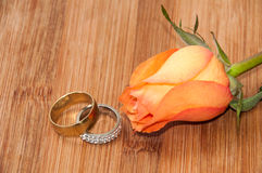 Pair of golden rings with orange rose on wooden board Royalty Free Stock Image