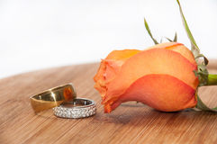 Pair of golden rings with orange rose on wooden board Stock Photos