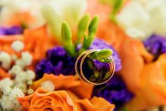 Pair of golden wedding rings inside bridal bouquet. Symbol of love and marriage on orange roses and eustoma (or Lisianthus). Tradi. Wedding rings on the twig of Royalty Free Stock Photo
