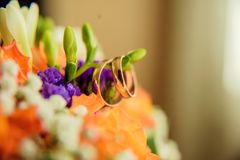 Pair of golden wedding rings inside bridal bouquet. Symbol of love and marriage on orange roses and eustoma (or Lisianthus). Tradi. Wedding rings on the twig of Royalty Free Stock Images