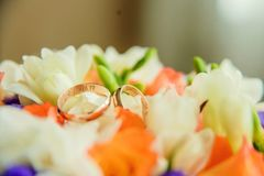 Pair of golden wedding rings inside bridal bouquet. Symbol of love and marriage on orange roses and eustoma (or Lisianthus). Tradi. Wedding rings on the twig of Stock Photography