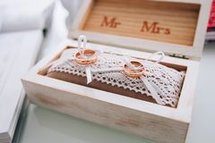 A pair of golden wedding rings lying in a white wooden box. Wedding decoration. Symbol of family, unity and love Stock Photo